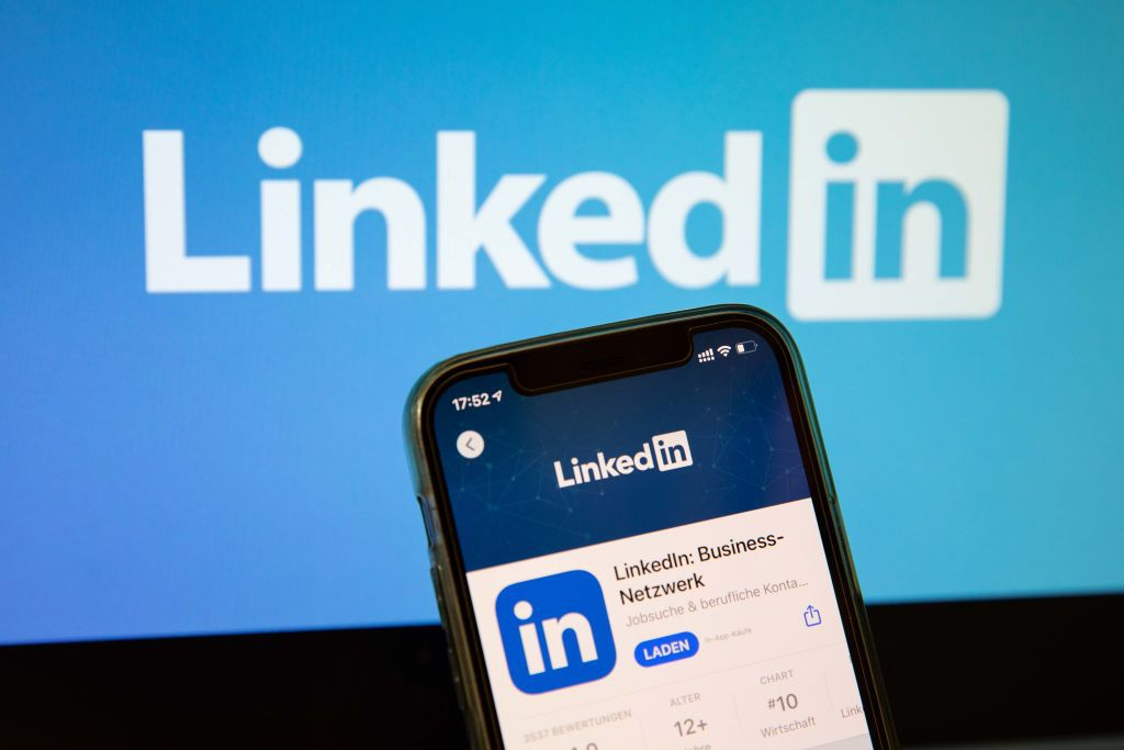 Closeup of a smartphone showing the LinkedIn app (German version) with a LinkedIn logo on a screen behind it.