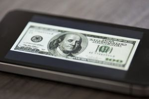 A miniature hundred dollar bill placed on top of a smartphone.