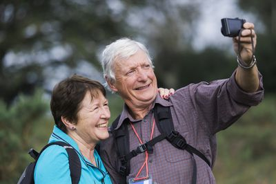 A senior couple taking a selfie with a digital camera