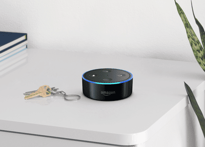 An Amazon Echo dot sitting on a shelf.