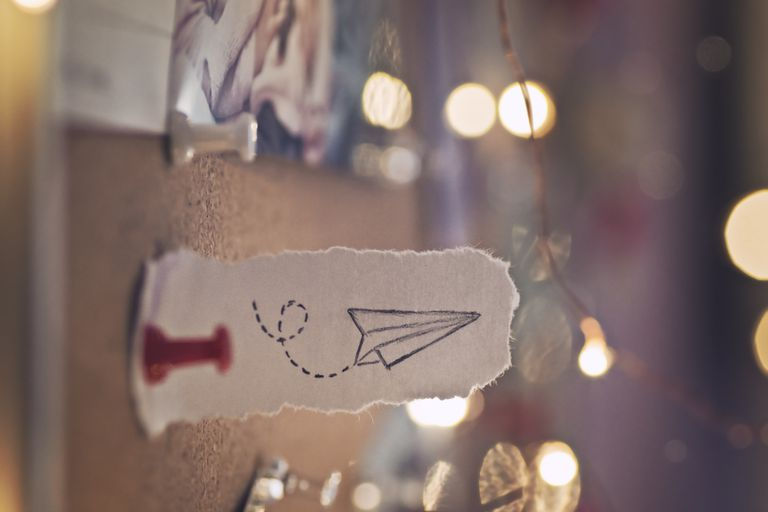 Paper with a drawing of a plane pinned to a corkboard