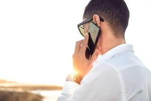 A business person talking on a Samsung phone outdoors.