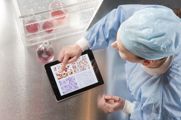 iPad being used by a woman in sterile hospital garb next to a display of petri dishes