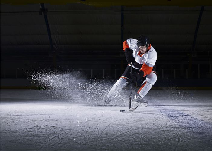 Ice hockey player receiving puck at high speed as ices flies through the air, wearing full protective clothing.