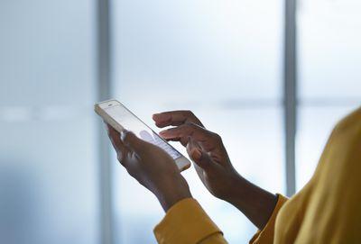 Woman in yellow shirt scrolling through white iPhone.