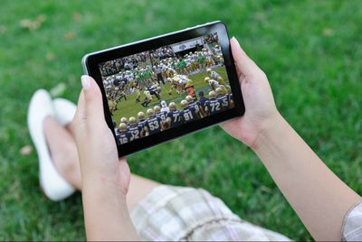 Someone watching football outside on a tablet.