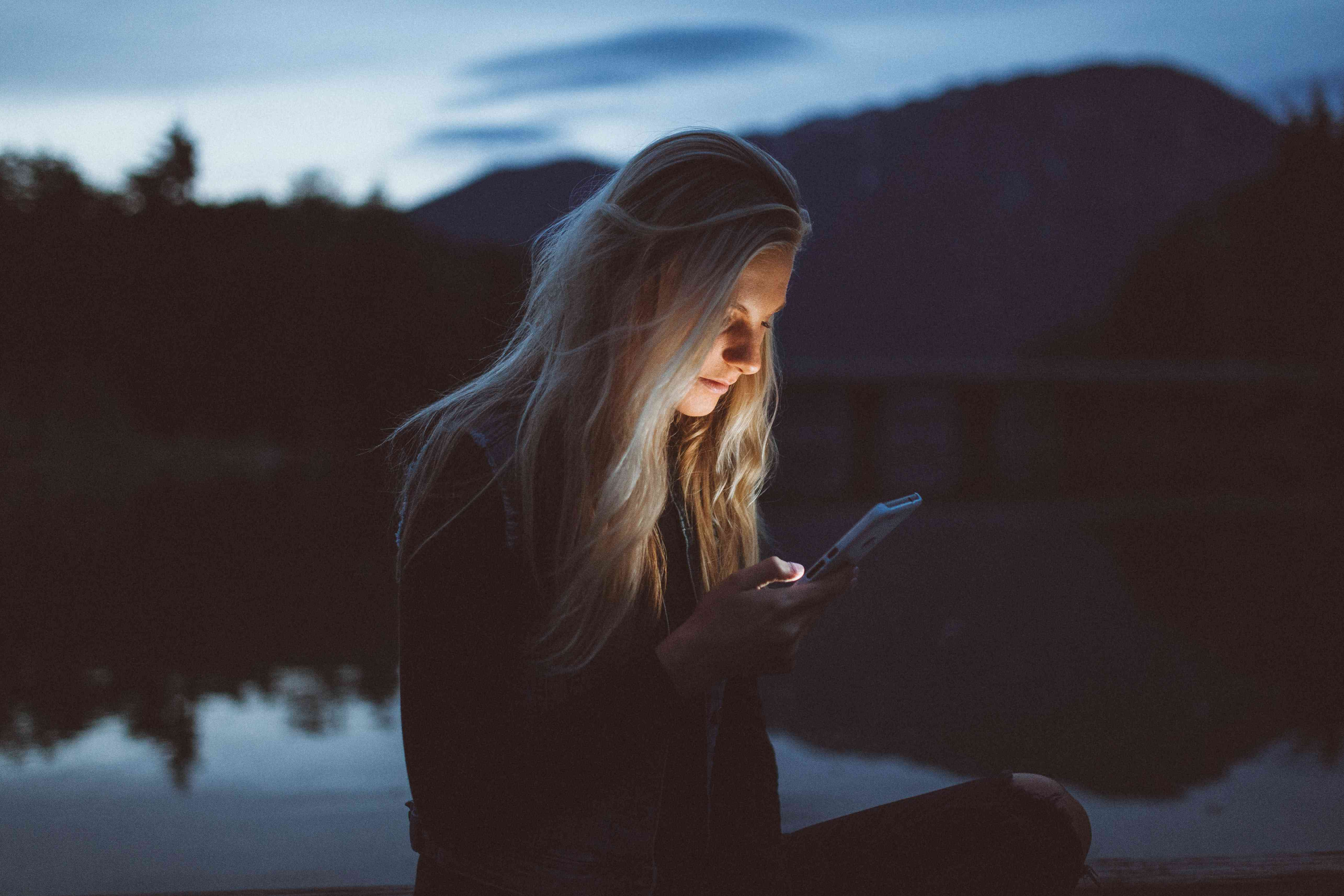 Someone messaging on a smartphone at dusk outside.
