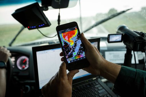 A storm chaser uses a radar app on his phone.