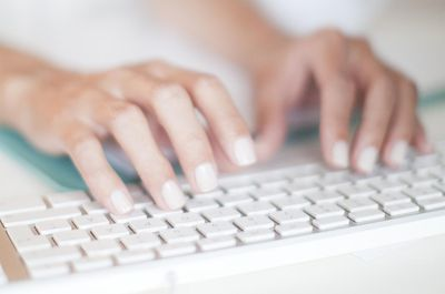 Woman typing on white keyboard