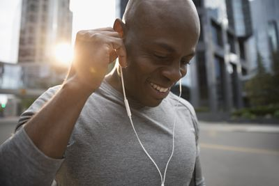 Runner listening to music with earbud headphones on urban street