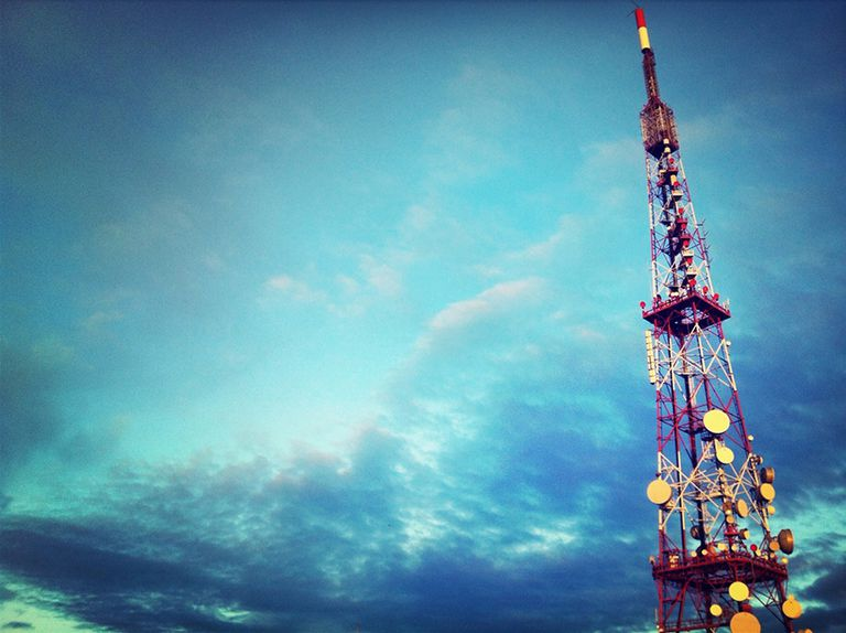 Radio transmitter tower against a partially cloudy blue sky