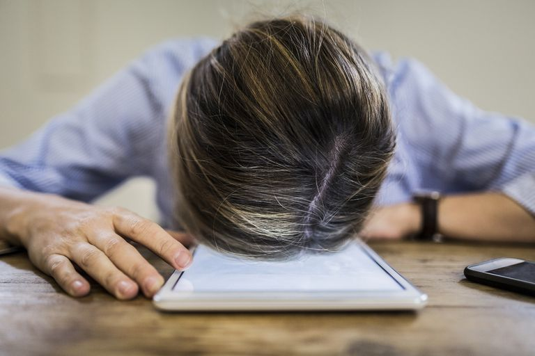 Man with head down on iPad that won't rotate