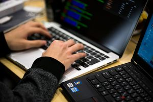 Hands on laptop, alongside another laptop