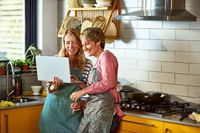 Two women leaning against a kitchen cabinet while looking at a laptop and smiling