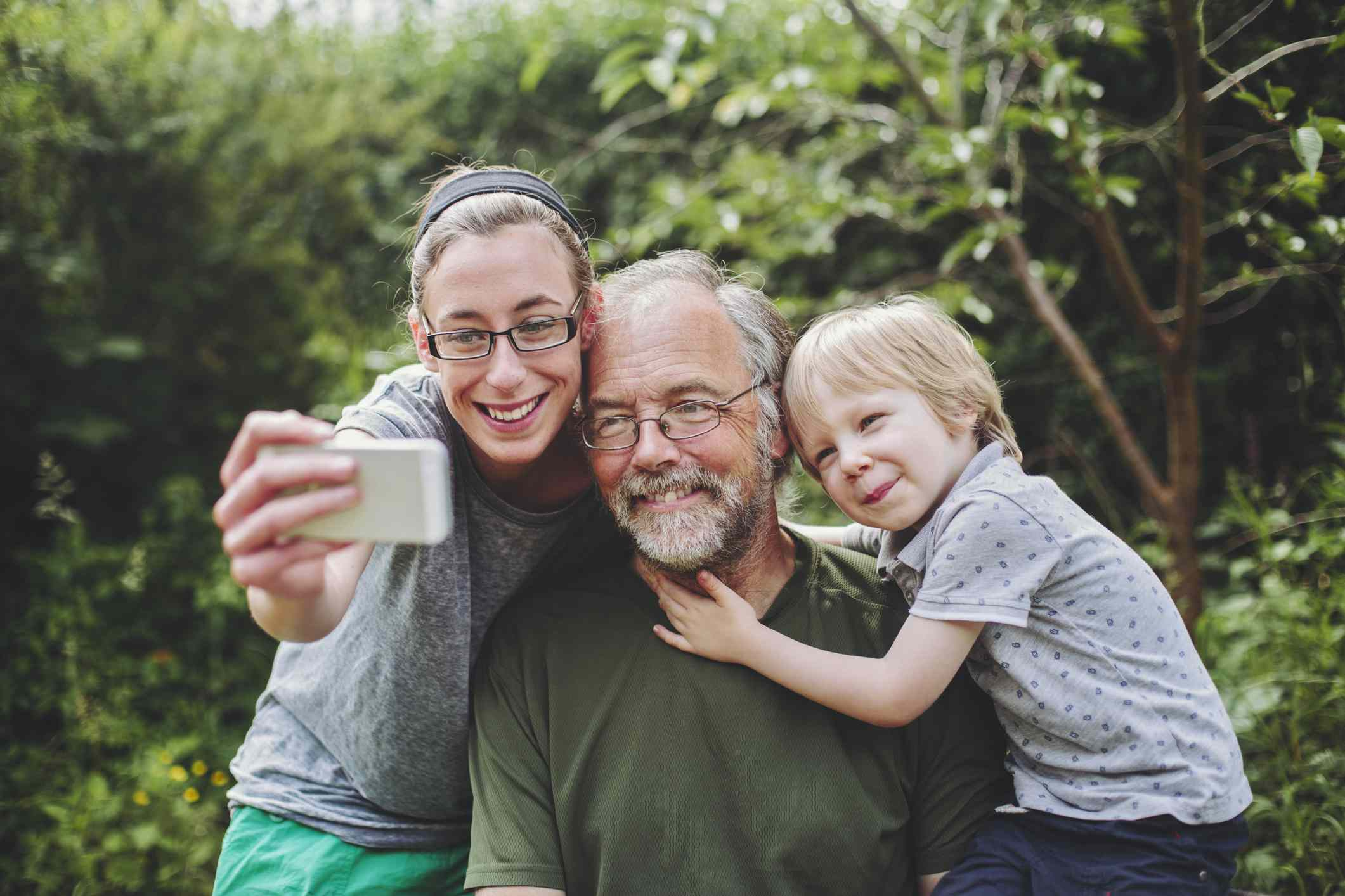 Man, woman, and child taking a selfie together in nature.