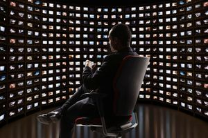 Man sitting in chair in front of a semi-circle of video monitors