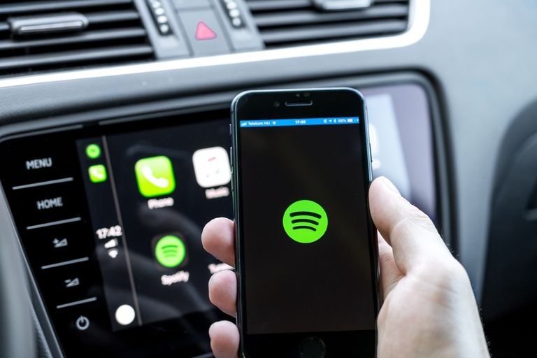Male hands holding a smartphone that is connecting to the car's computer running Spotify