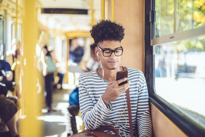 Young man looking at phone on bus