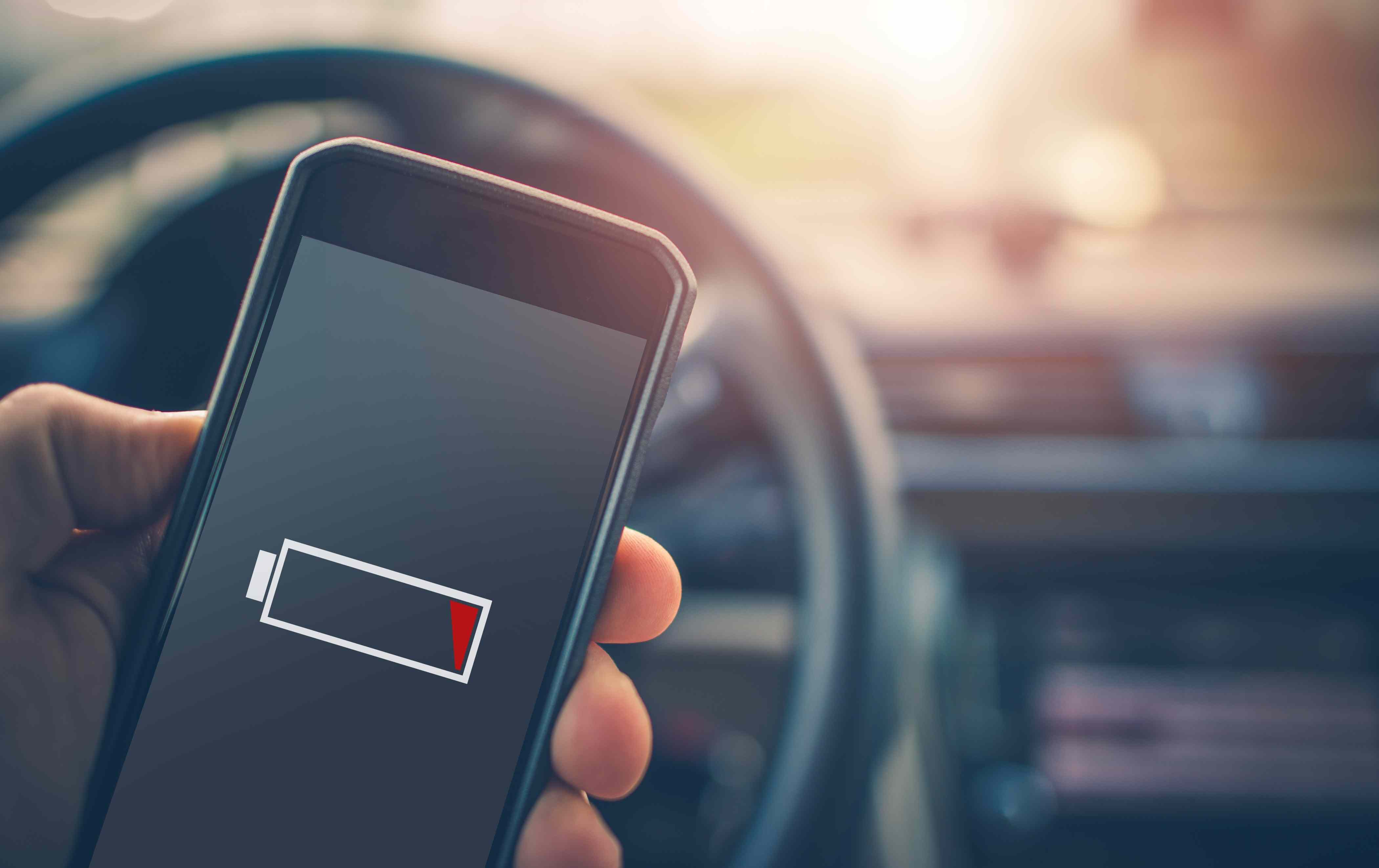 A hand holds a phone with a dead battery in a car