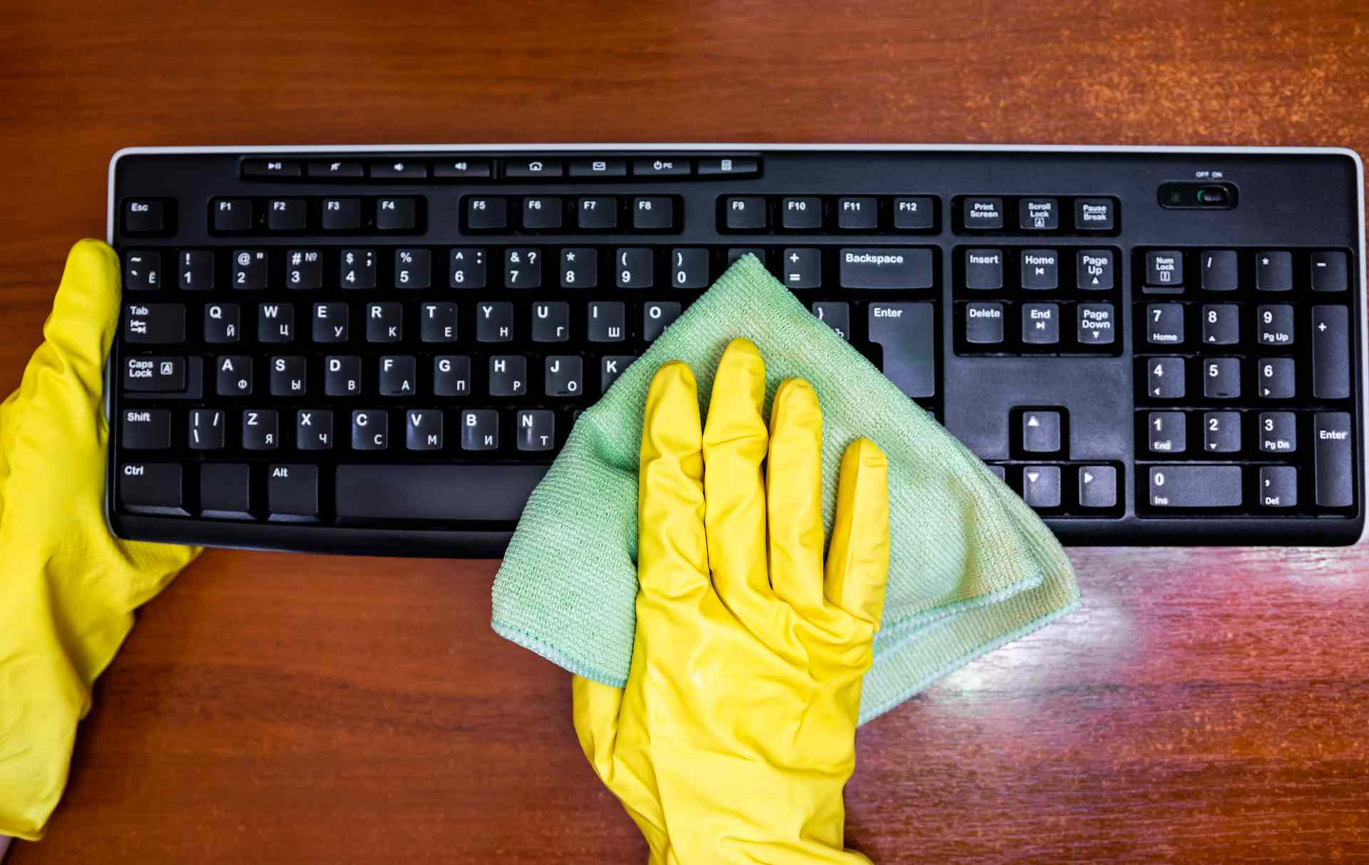 A woman wearing yellow gloves wiping down a black mechanical keyboard.