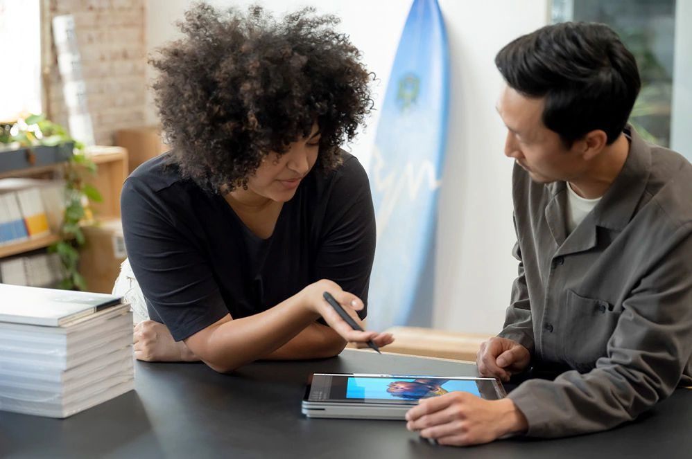 Two people collaborating on a Surface Pro Laptop in Tablet Mode.
