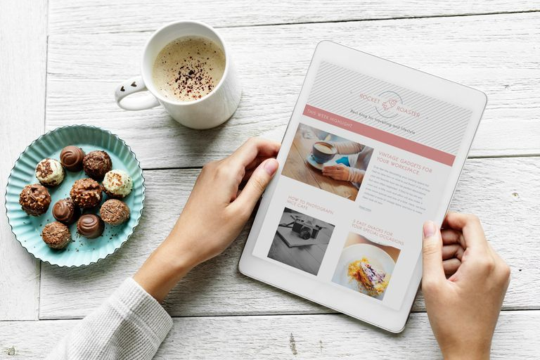 Stock photo of a person's hands holding a tablet that shows the front page of a travel blog.