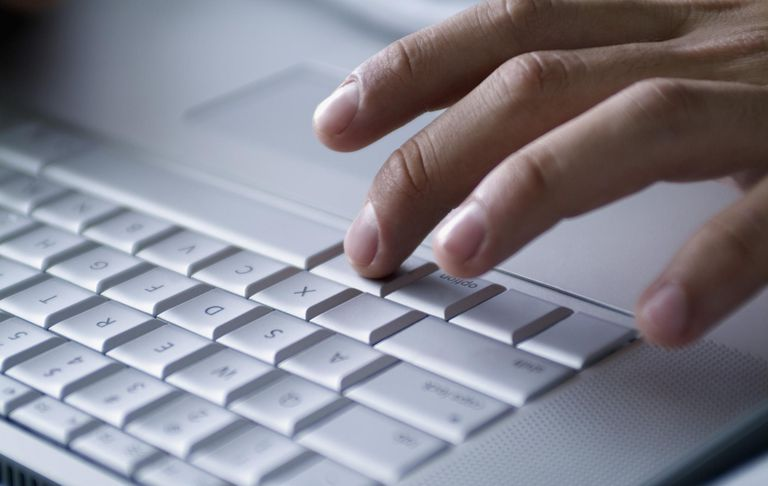 Hand typing on laptop computer, close-up
