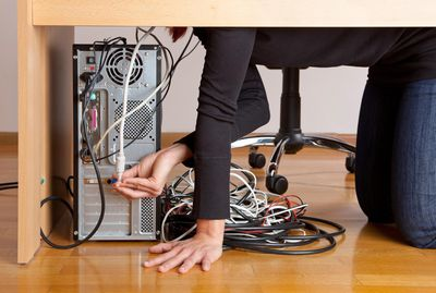 Person plugging in cables into a desktop computer
