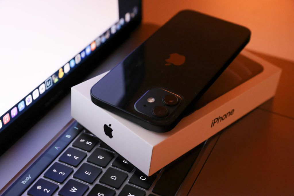 iPhone 12 on iPhone box set on top of MacBook