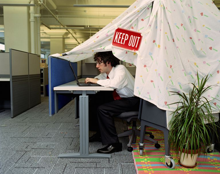 Male executive hiding under 'tent' in office