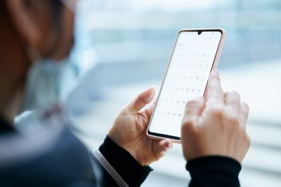 Someone looking at a calendar on a smartphone.