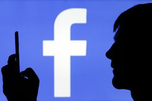 Facebook logo with shadow figure in front holding smartphone