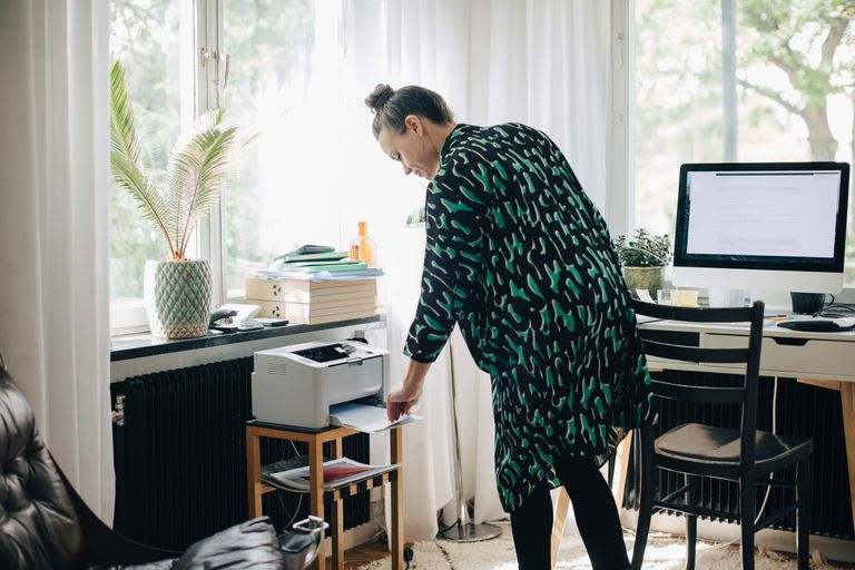 Woman using at home printer in home office next to computer
