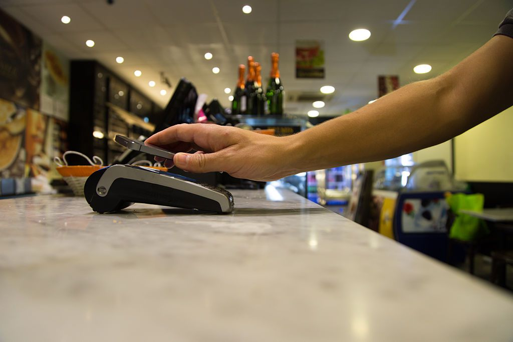 Person doing a contactless payment with smartphone application on a bakery.