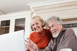 Senior couple using webcam on laptop
