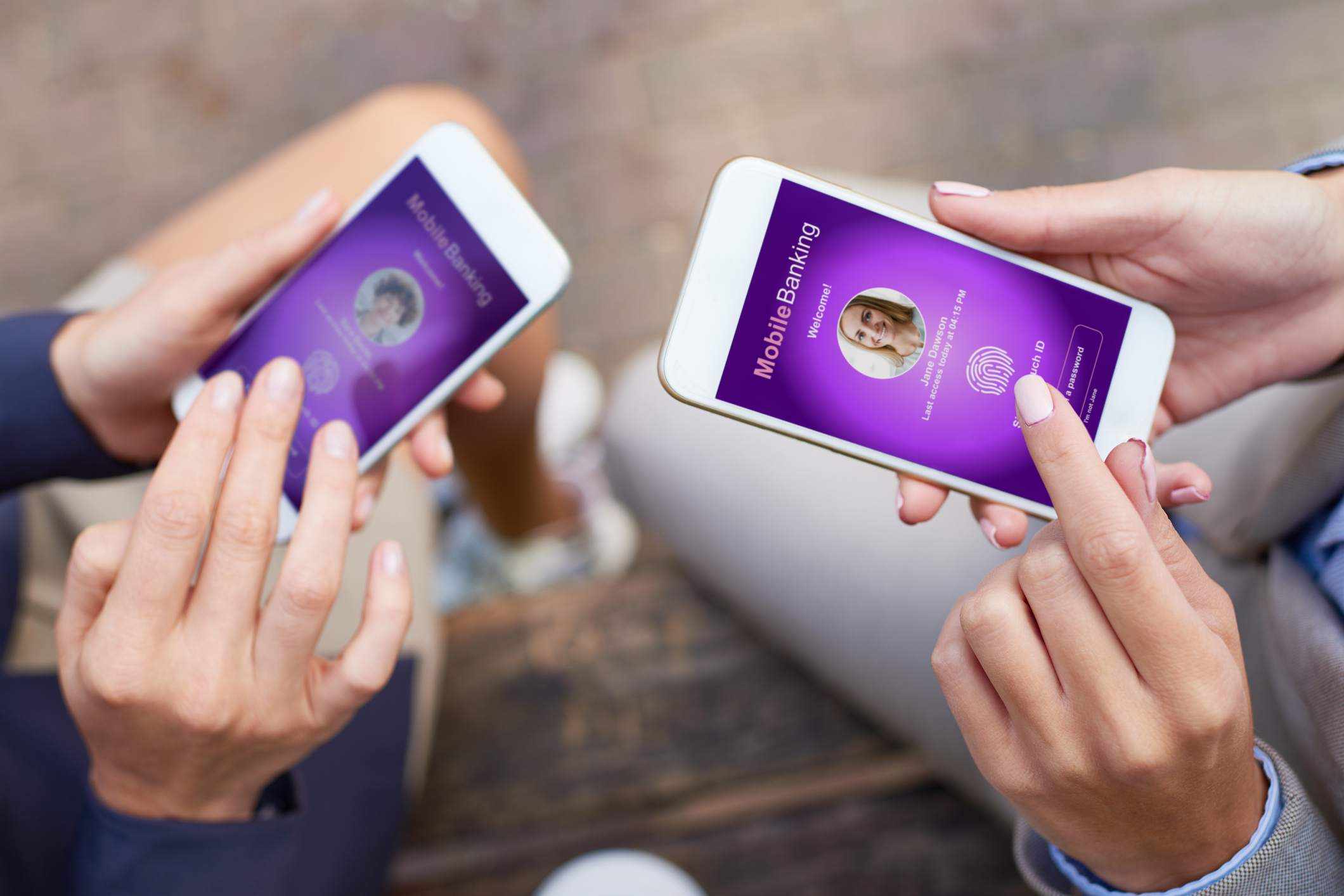A close up of hands holding smartphones using biometric access for mobile banking apps