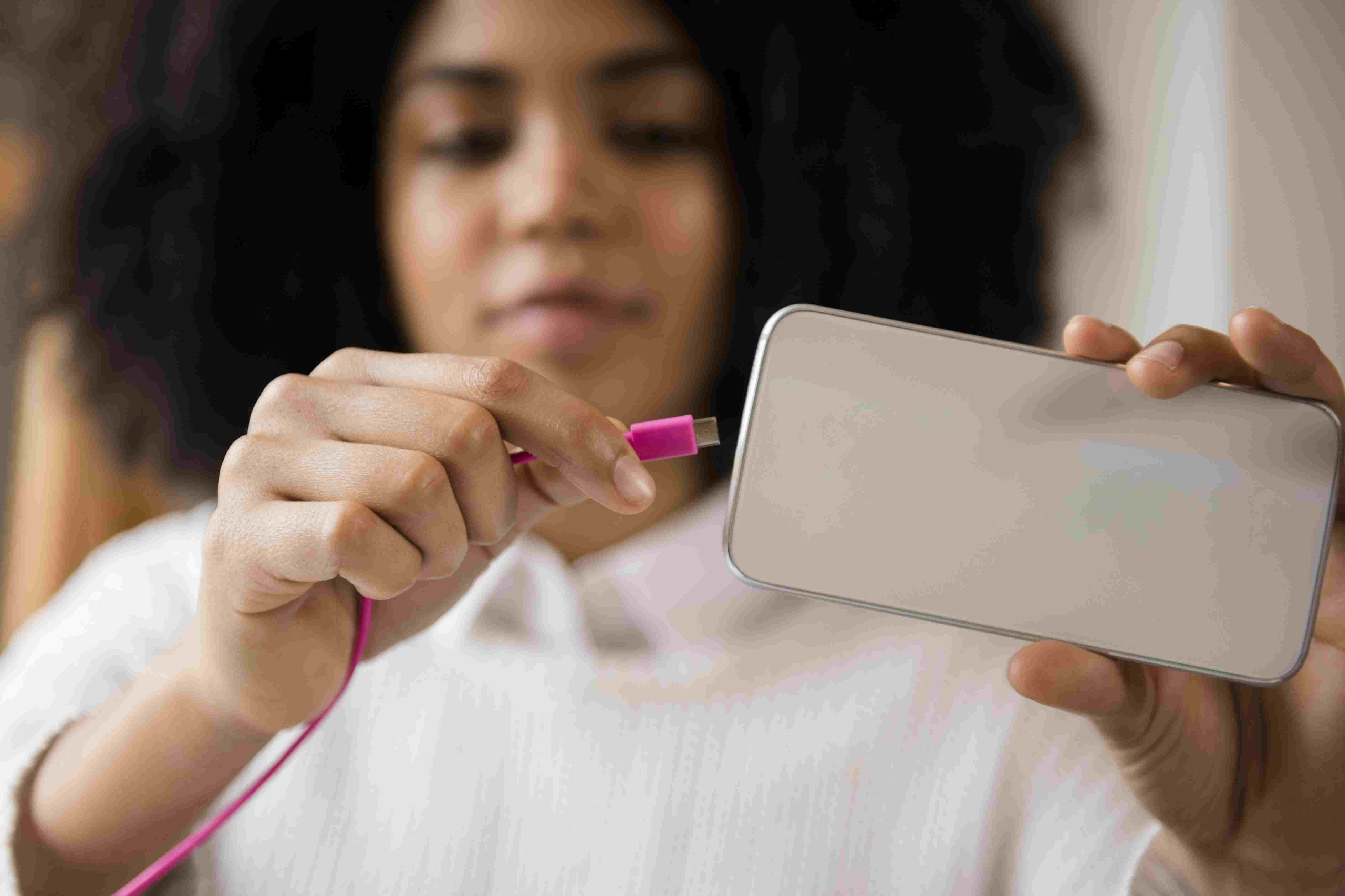 African American woman connecting cable to cell phone