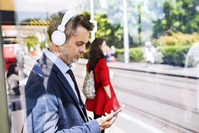 Man wearing closed back headphones waiting for the train
