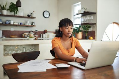 A woman sitting at a table in her kitchen with a laptop in front of her