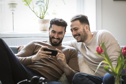 Two men laugh while watching TV on a smartphone