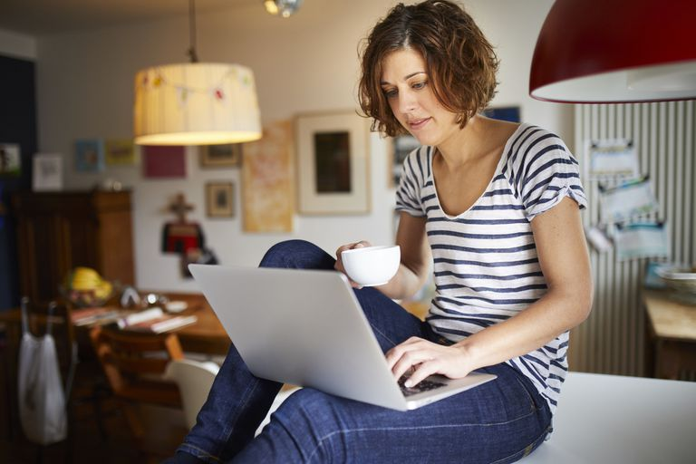 Woman in striped shirt using computer and holding a mug