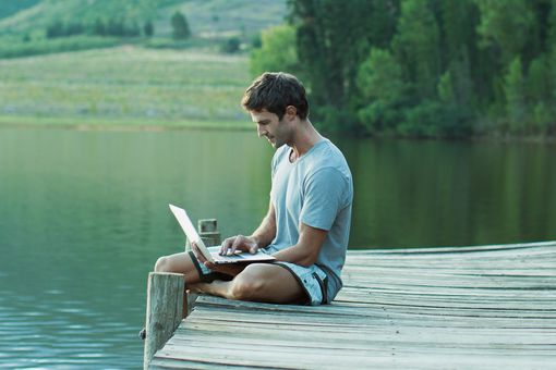A man using Windows 10 on a laptop while relaxing near a lake.