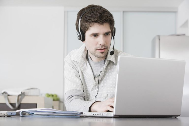 A man sitting, working with computer and wearing headset