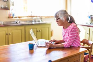 An older woman sitting at a kitchen table looking at her laptop