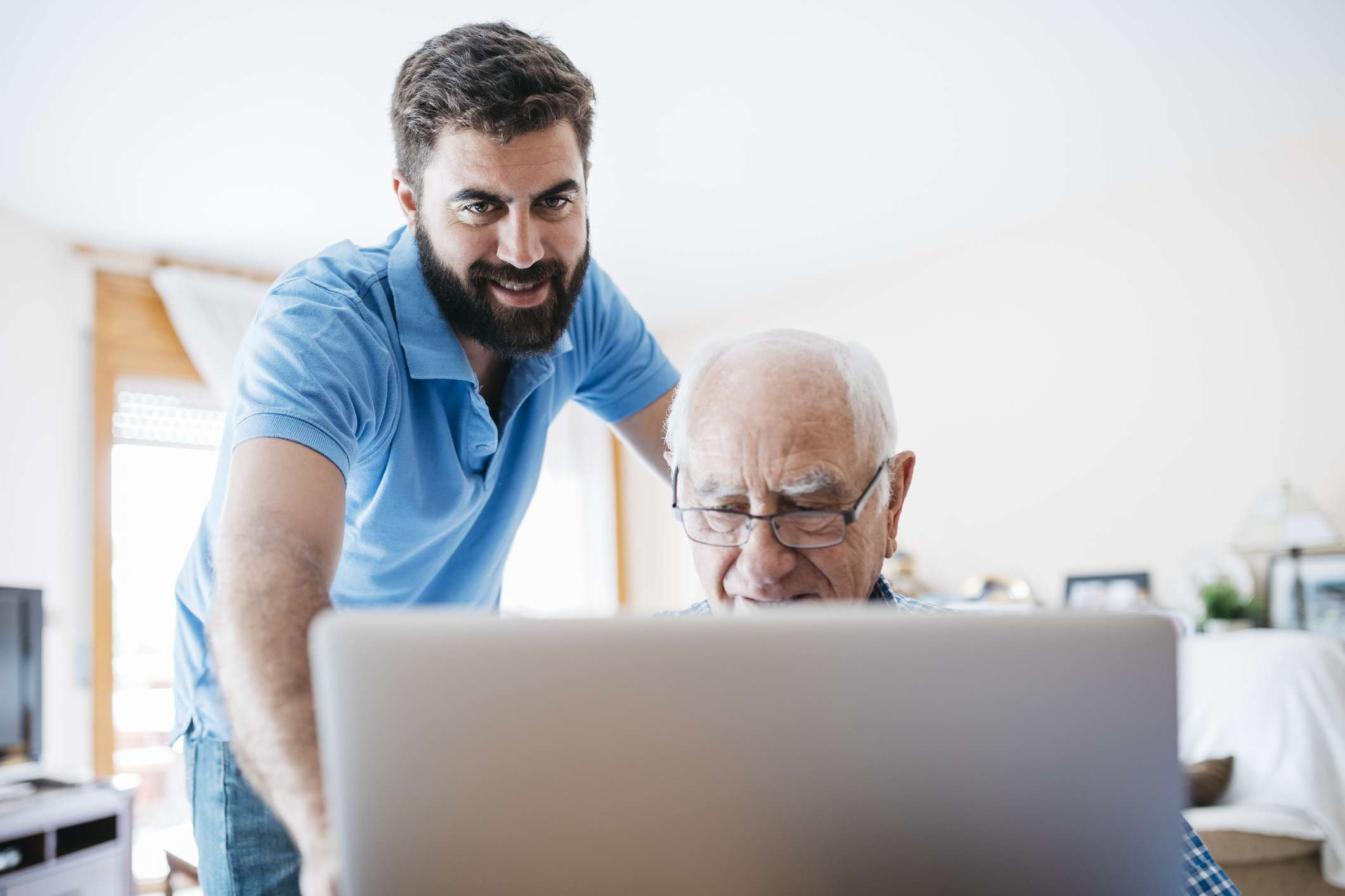 A younger adult helping an older adult at the computer.