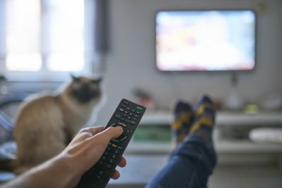 A close up of a remote held by someone sitting down with their feet up and watching TV with a cat nearby