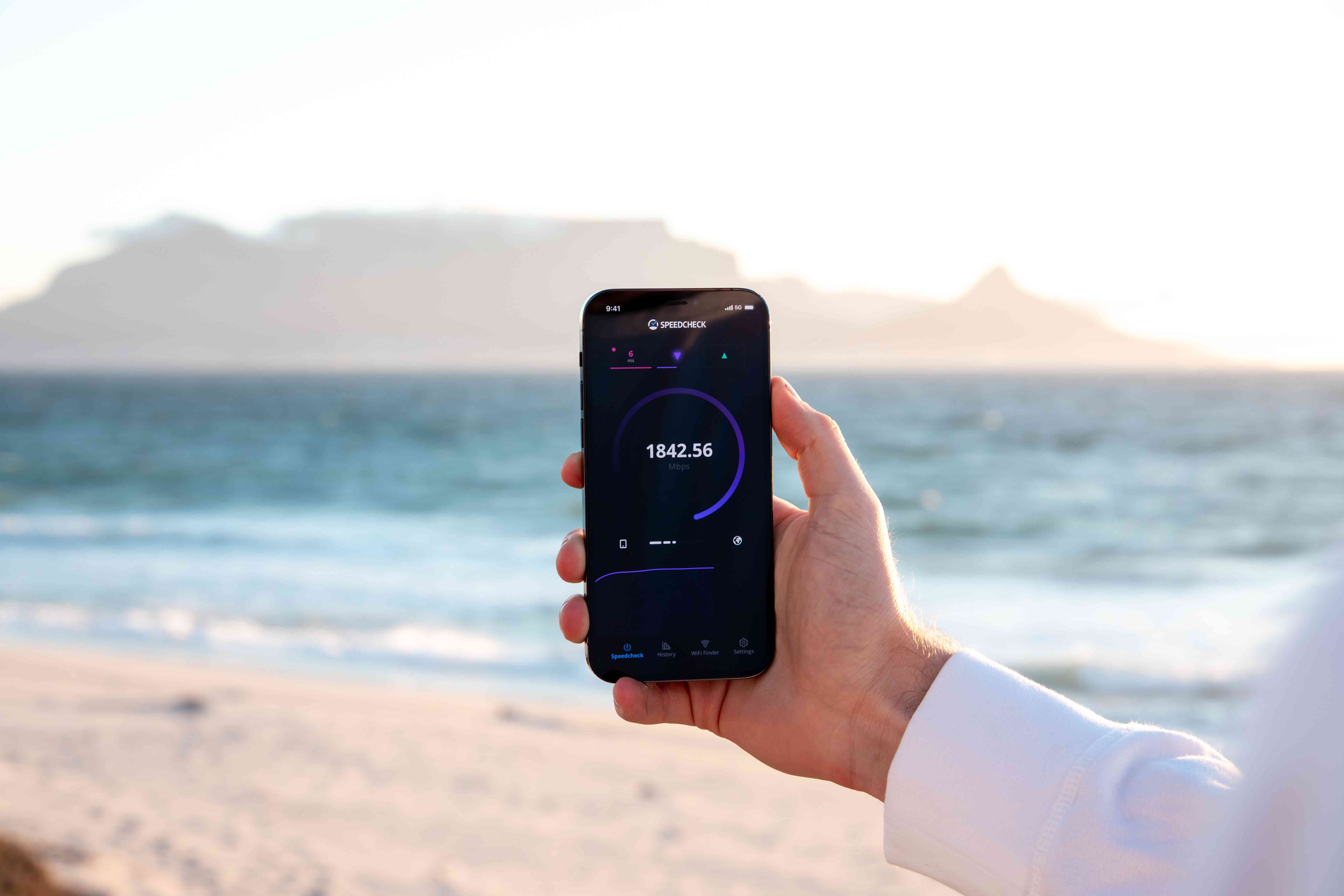 Hand holding phone with speed test on the screen, beach in the background