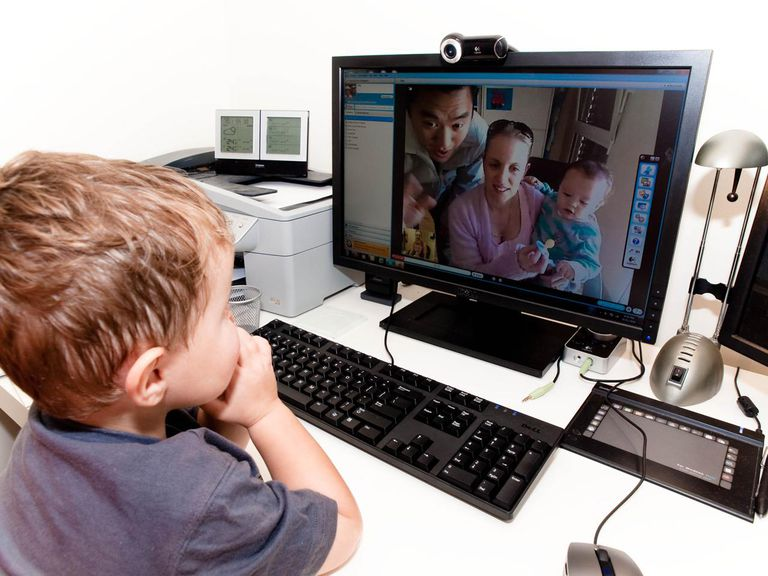 family using skype to talk to a child on a computer