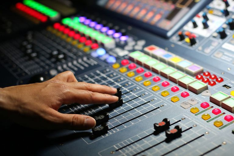 A hand moving controls on a soundboard