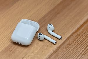 Apple AirPods and charging case on wooden blurred background.